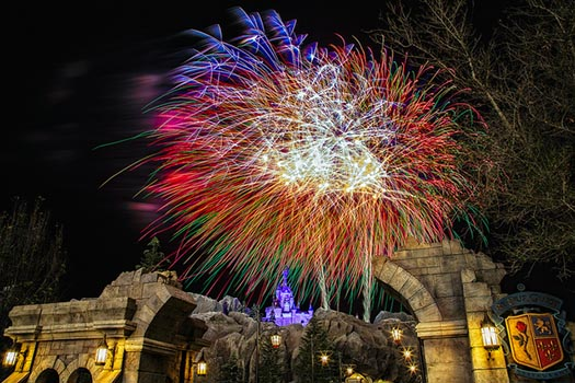 The Broken Arch outside Be Our Guest with the Beast's Castle in the background with fireworks breaking right over the castle