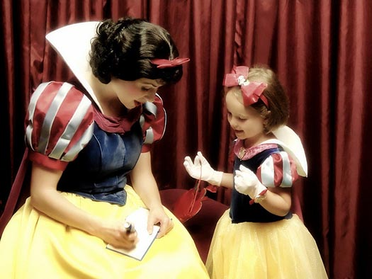 Snow White signs an autograph for a little Snow White