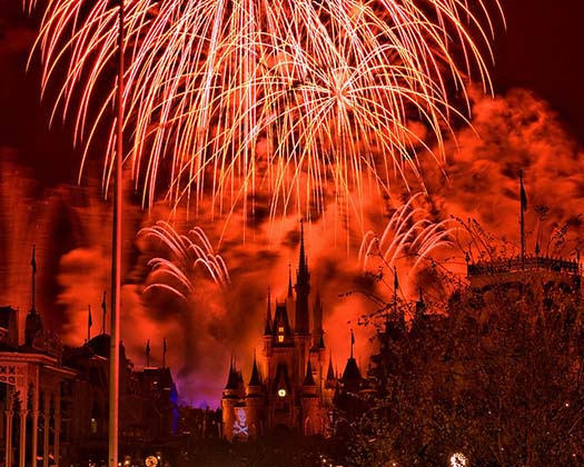 Hallowishes with an orange glow over Cinderella Castle