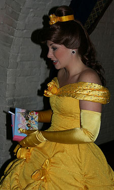 Belle from Beauty and the Beast in a yellow dress signing autographs