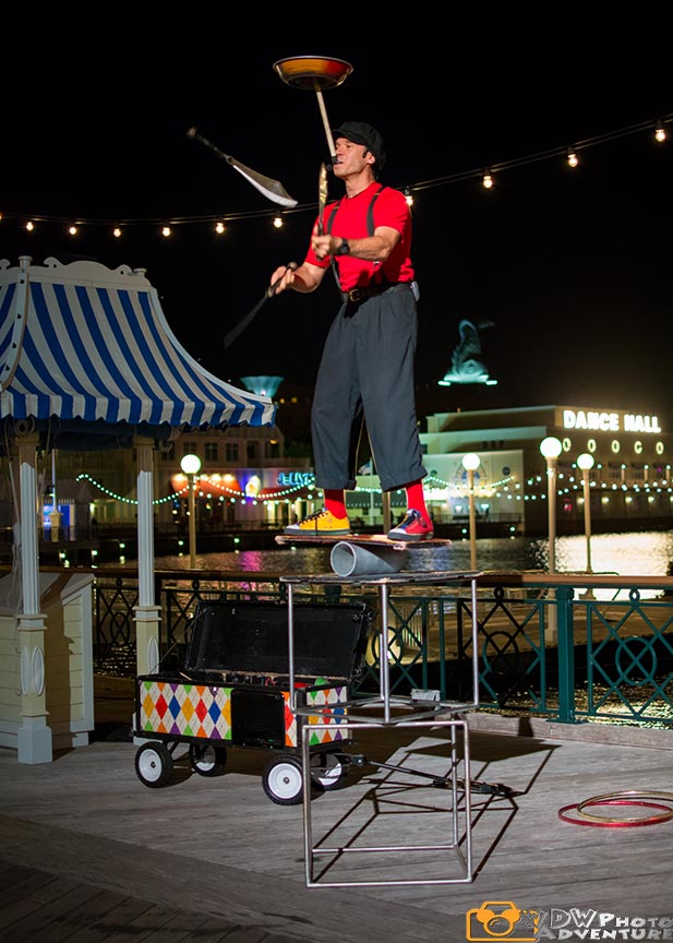 A nighttime entertainer riding a unicycle and juggling on the Boardwalk