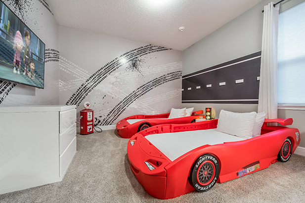 A bedroom with race car beds