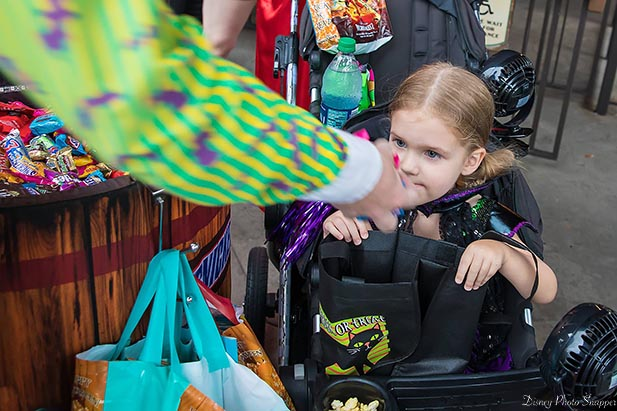 Aubrey is filling  up her bag of candy at Mickey's Not So Scary Halloween Party