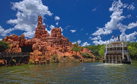 The Liberty Belle on the Rivers of America on a beautiful day with Big Thunder Mountain in the background