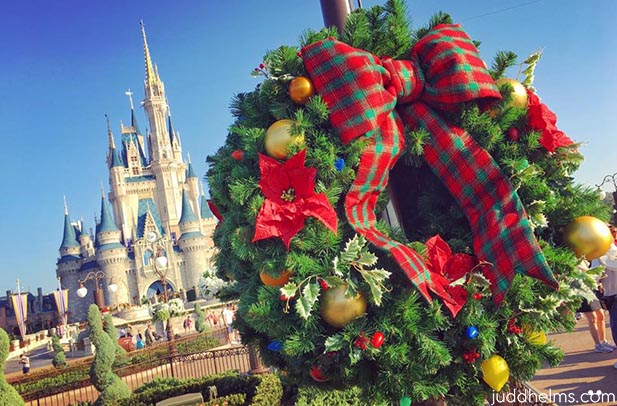A Christmas wreath on Main Street with Cinderella Castle in the background
