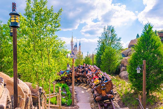 A group of people riding the Seven Dwarfs Mine Train