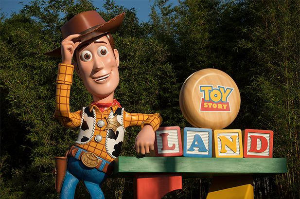 Woody sitting on blocks welcoming you to Toy Story Land