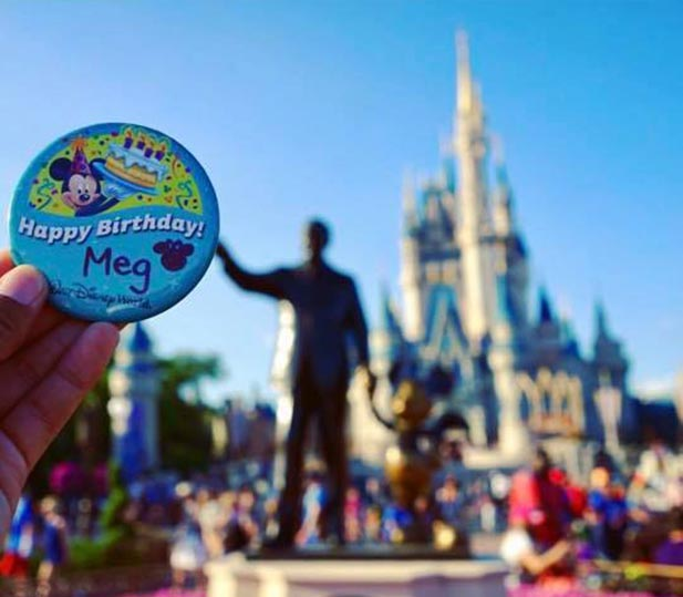 A Happy Birthday button held up in front of Cinderella Castle
