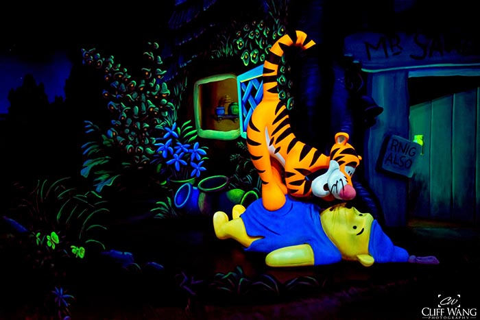 Tigger is on top of Winnie the Pooh